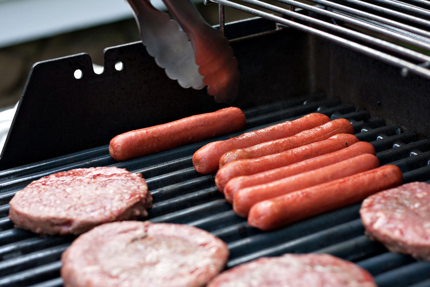 close up photo of hamburgers and hotdogs on the grill
