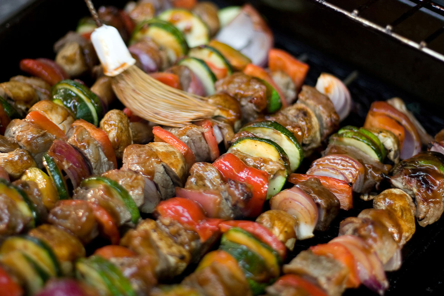 picture of basting kebabs of beef, onion, zucchini and red peppers over a grill