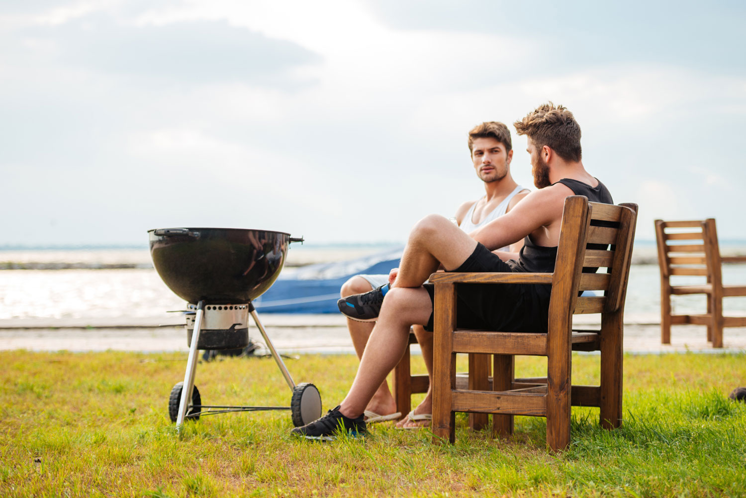 two guys chatting by a lake next to a weber kettle