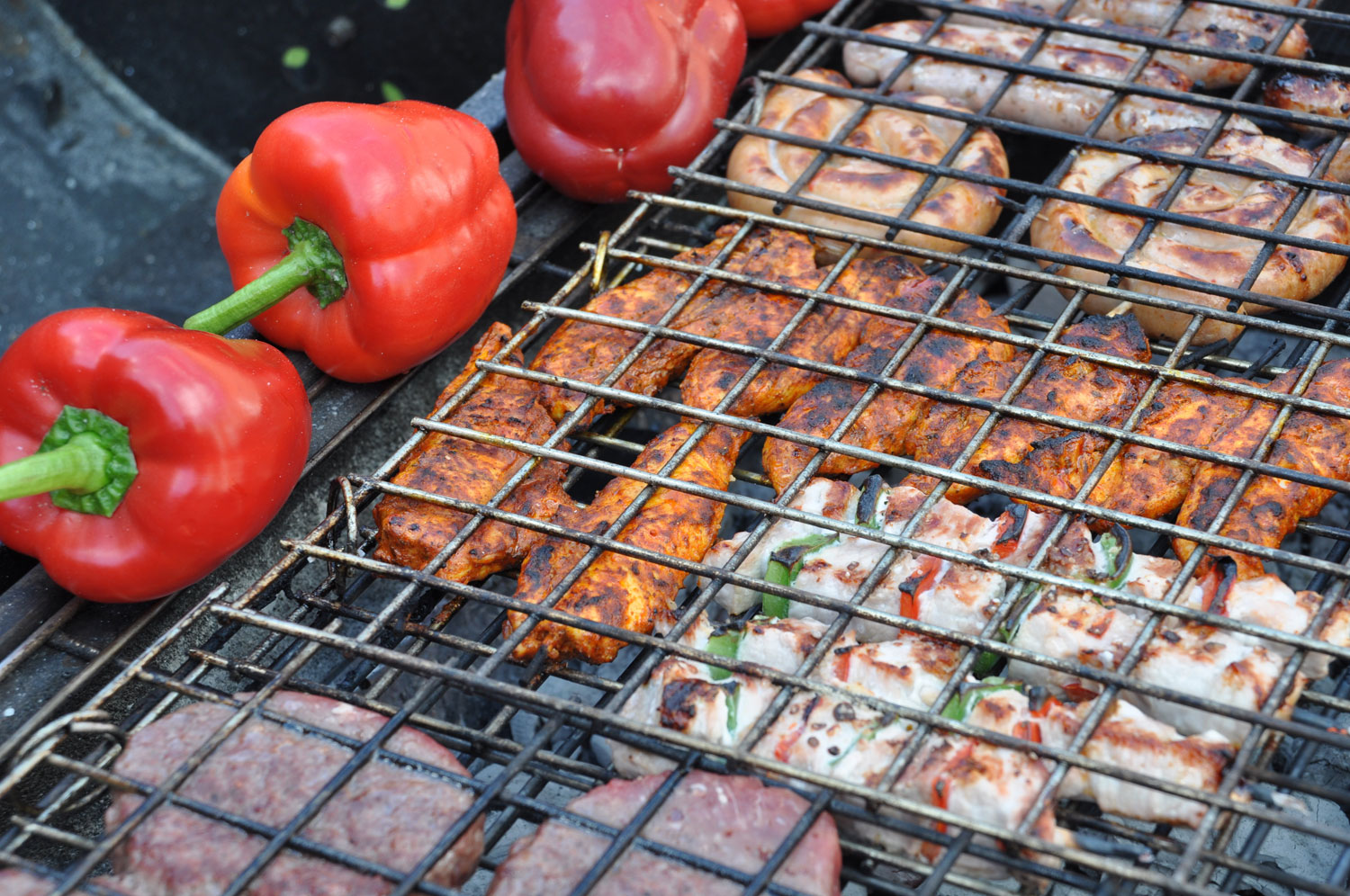 photo of meats and vegetables being grilled outside over charcoal