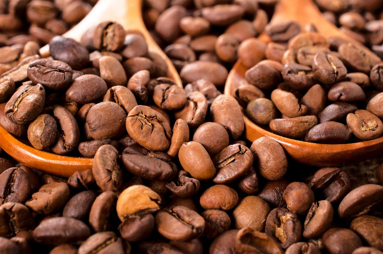 zoomed in photograph of coffee beans in and around wooden spoons
