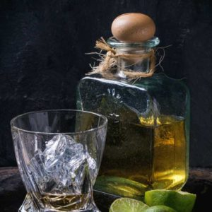bottle of tequila with a shot in a rocks glass plus cut limes